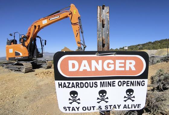Heavy equipment is used to cover a mine shaft, one of about 6,000 that have been sealed in the U.S. so far. (AP)