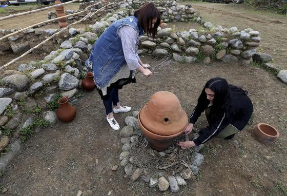 Assistants arrange wood under a replica 5th millennium B.C. perfume distiller. Cyprus was long known for the quality of its perfumes. (AP