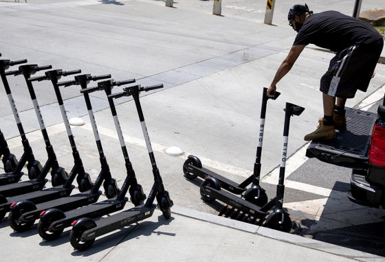 James Wilson lines up electric scooters on a street corner after charging them overnight in Atlanta, Georgia. Scooters are now common in many cities around the world. (AP)