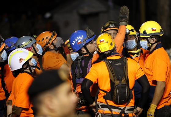 The leader of the Chilean rescuers, center, gives his team direction in where to start searching the site. (AP)