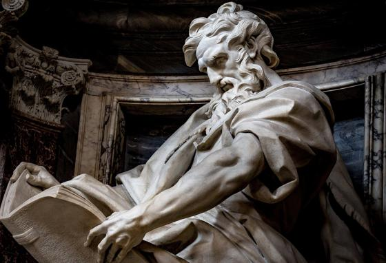 A statue of the apostle Matthew holding out the gospel he wrote