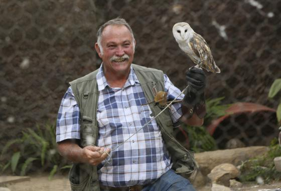 Gary Strafford holds an owl inside one of the cages at Kuimba Shiri. (AP)