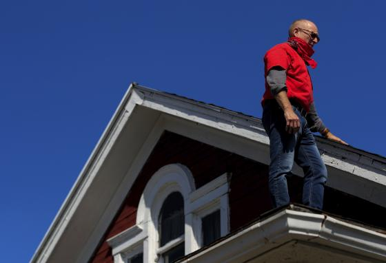 Gary Zaremba inspects the roof of one of his properties. Landlords must pay for mortgages, repairs, and other expenses. They depend on renters for money. (AP)