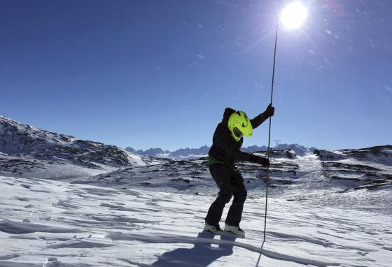 A geologist uses an avalanche probe to measure snow depth at Thompson Pass, Alaska. One program recruited citizen scientists to measure snow levels in mountain terrain. (AP)