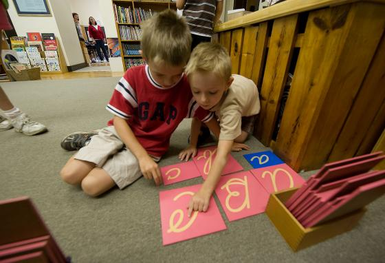 Davis Payne, left, and Brendon Farmer trace cursive letters with their fingers at the Mountaineer Montessori School. (AP/Bob Bird)