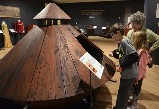 Kids peer into a wooden battle tank modeled after one designed by Leonardo da Vinci at a