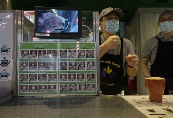 A staff member gestures behind the counter with a board showing sign language instructions. (AP/Vincent Yu)