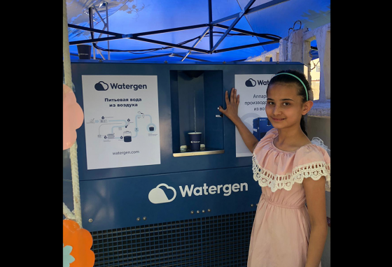 A girl gets a cup of clean drinking water from the Watergen machine. (Watergen)