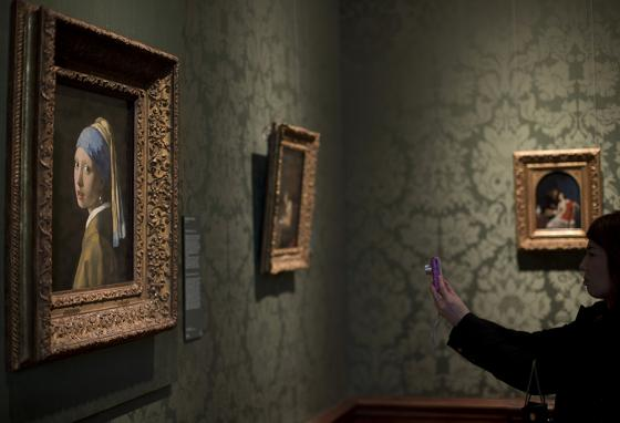 A visitor photographs Girl with a Pearl Earring at the Mauritshuis Museum in The Hague, the Netherlands.  (AP)