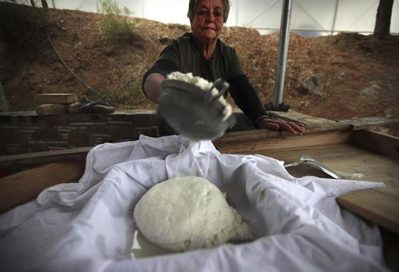 Aphrodite Philippou, 73, strains the halloumi in cheesecloth to squeeze the whey out while shaping it. (AP)