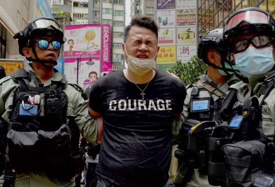 Police hold a protester after spraying pepper spray during a protest in Hong Kong. (AP)