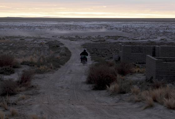 An Uru man rides a motorcycle near the lake bed. Bolivia's second-largest lake dried up about five years ago. (AP/Juan Karita)