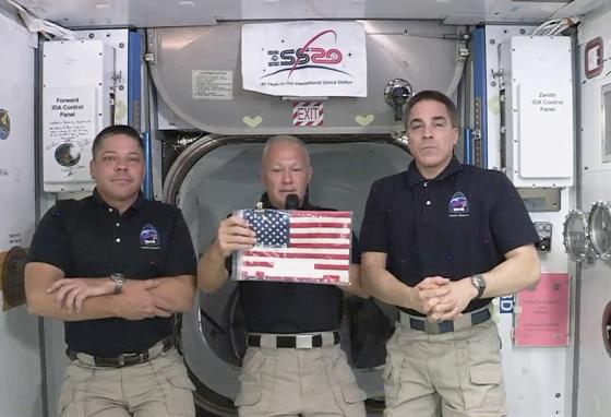 Commander Douglas Hurley (center) speaks about their mission to bring back the American flag left at the International Space Station nearly a decade ago. (AP)