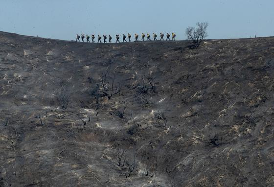 Fire crews often work in close groups to fight these large wildfires. (AP)