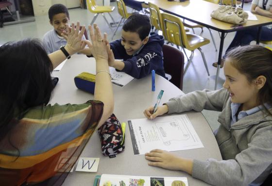 Teacher Julia Puentes, left, high-fives student Mathew Botros, age nine, center, during an English class at a bilingual school in Miami. (AP/Lynne Sladky)