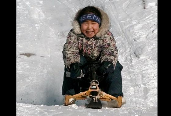 An Inuit girl steers her sled down a hill in her hometown in Canada. (AP)