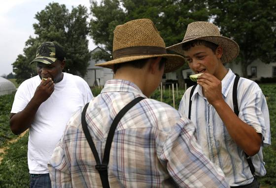 James Chase (left) shares slices of melon with boys belonging to an Old Order Mennonite family at the family's farm. (AP)