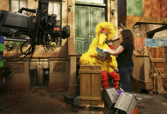 Camera and stage crew members help Big Bird and kids get ready for a scene on the Sesame Street set. (AP)