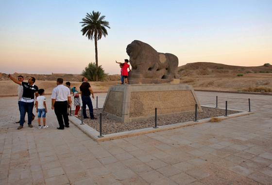 Tourists stand near the Lion of Babylon. (AP)