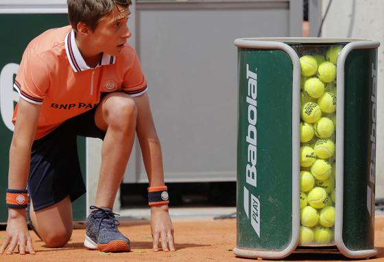 On a clay court at the French Open tournament in Paris, France, ball boys and ball girls get set to charge out and scoop up balls when a volley is finished. (AP)