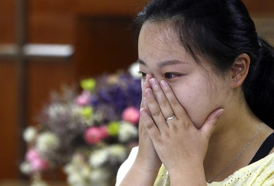 Ren Ruiting, daughter of Liao Qiang, cries as she speaks during an interview with a reporter at a church in Taipei, Taiwan. (AP)