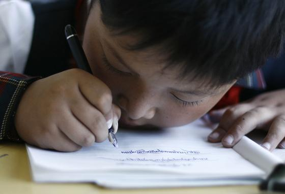 A boy practices writing in China. Focusing on close work tires the eyes. Computer and phone screens make it even worse. (AP)