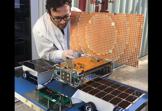 An engineer uses sunlight to test the solar panels on a Mars CubeSat. (AP)