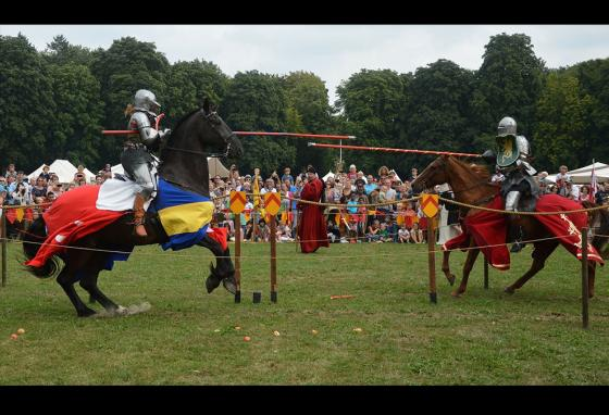Men try to knock each other off their horses during a jousting match.