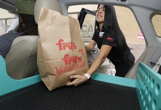 A supermarket worker puts groceries into the self-driving Nuro vehicle, to be tested in Scottsdale, Arizona. (AP)