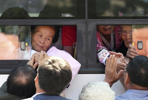 North Koreans on a bus hold the hands of their South Korean relatives, saying goodbye after the reunion. (AP)