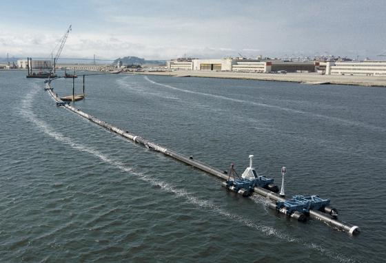 A test section of the floating boom that will be used to corral plastic litter is towed out into the Pacific Ocean. (AP)