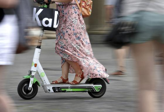 A woman drives an electric scooter through a public square in front of the Brandenburg Gate in Berlin, Germany. (AP)