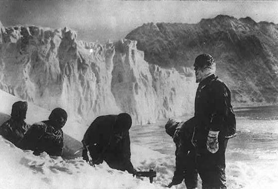 Men with Ernest Shackleton's expedition to the Antarctic try to survive the cold by digging a dwelling hole in the ice on Elephant Island. (LOC)