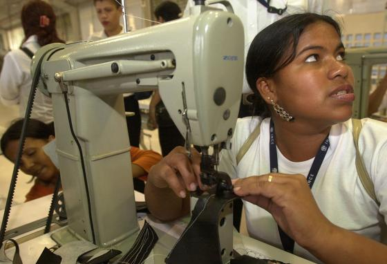 Marielis Durrego learns to sew in a shoe making factory. Some oil wealth was spent on the poor. But unwise programs discouraged businesses. (AP)