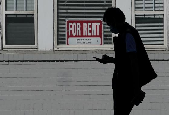 A man walks in front of a For Rent sign in a window of a property in San Francisco, California. (AP)
