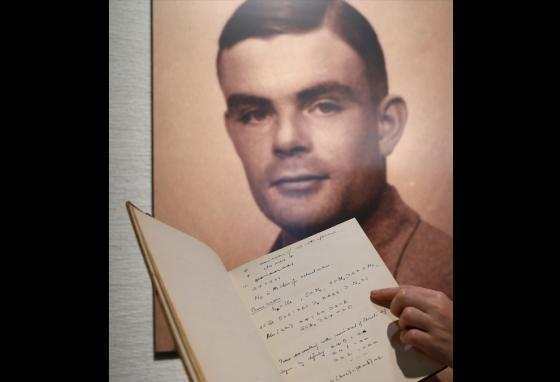A page from the notebook of Alan Turing is displayed in front of his portrait. Mr. Turing designed the Bombe machine at Bletchley Park. (AP)