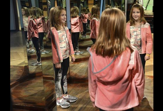 MacKenzie Heinaman stands in a room of small mirrors like one designed by Leonardo da Vinci at an exhibit in Charleston, West Virginia. (AP)