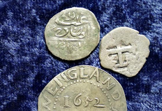 The Arabian silver coin, top, is shown near an Oak Tree Shilling minted in 1652 by the Massachusetts Bay Colony, below, and a Spanish half real coin from 1727, right. (AP/Steven Senne)