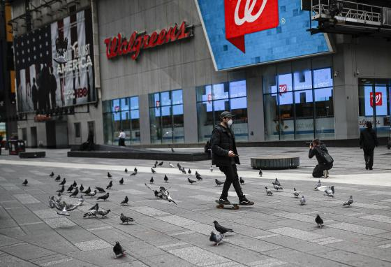 A skateboarder passes through a flock of pigeons in Times Square in New York City. (AP/John Minchillo)
