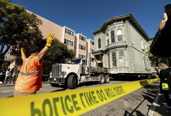 A worker signals to a truck driver pulling the house. (AP/Noah Berger)