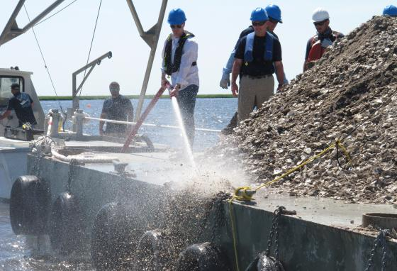 New Jersey Environmental Protection Commissioner Shawn LaTourette, left, uses a high-pressure hose to blast clam and oyster shells into the Mullica River. (AP/Wayne Parry)