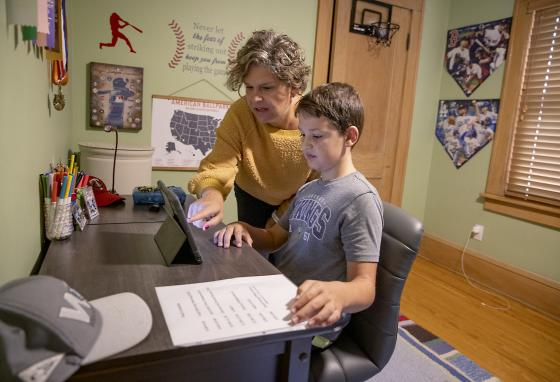 Paul Hendricks receives some help from his mother Anne as he attends his first day of 5th grade from his bedroom in St. Paul, Minnesota. Many schools have gone online this year. (AP)