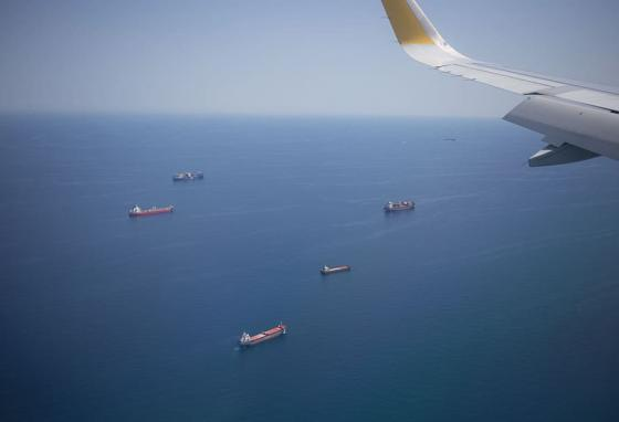 A camera in an overhead plane spots a fleet of cargo ships on their way.