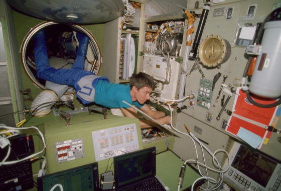Sergei K. Krikalev works with his feet anchored in a tunnel hatchway. The first crew spent most of their time trying to get equipment to work. (NASA via AP)