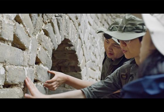 Members of the Intel team look at the brickwork of the wall. (Intel)