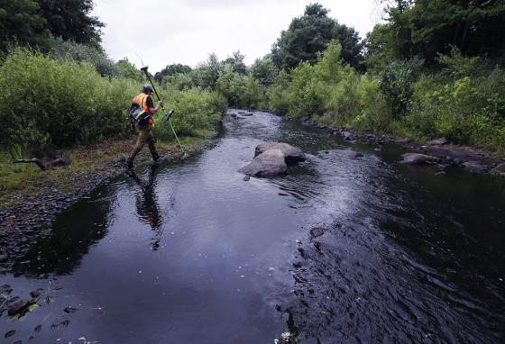 A surveyor walks the banks of the Mill River at the site of the former Whittenton Pond Dam, which was removed due to its dangerous condition. (AP)
