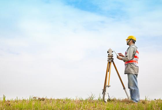 A surveyor uses a transit while making land calculations.