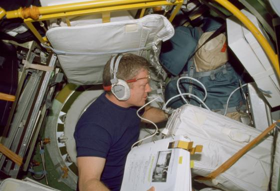Bill Shepherd works in a docking compartment aboard the ISS. (NASA via AP)