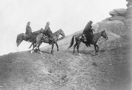 Three Navajo Indians on horseback make their way over hilly terrain in 1906. (LOC)