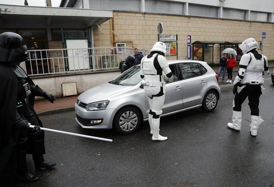 Men dressed as Stormtroopers joke with people in a car outside a lightsaber tournament in France. (AP)